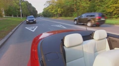 Car traffic on road behind red cabriolet at autumn sunny day Stock Footage