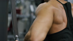 View of a  muscular weightlifters arm and back as he works out Stock Footage