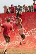 Competitors Attempt To Climb Wall In Extreme Obstacle Course Race - stock photo