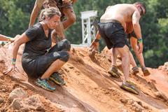 Competitors Slide Down Slippery Hill At Extreme Obstacle Course Race Stock Photos