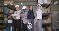 4K Portrait of serious mixed ethnicity management team in industrial warehouse.  Stock Footage