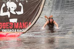 Man Goes Headfirst Down Water Slide In Obstacle Course Race Stock Photos