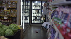 Man in grocery store finds wallet on the floor, and picks it up. Stock Footage