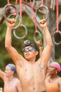Man Holds Onto Suspended Rings At Extreme Obstacle Course Race - stock photo