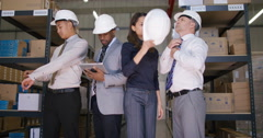 4K Portrait of serious mixed ethnicity management team in industrial warehouse.  - stock footage