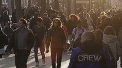 Back-lit crowd of people walking on street Stock Footage