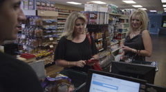 Two women at the grocery store register, one offers to pay for the other. Stock Footage