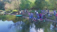 People launch toy ships on pond in park at autumn sunny day Stock Footage