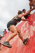 Woman Gets Assist Climbing Wall In Extreme Obstacle Course Race - stock photo