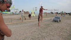 Woman Walking on Slackline with the help of another woman on The Coast Stock Footage
