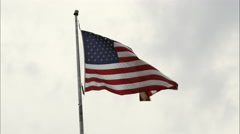 United States' flag waving in the wind with partially cloudy sky. Stock Footage