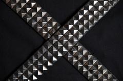 Rocker spike belts crossed on a black background - stock photo