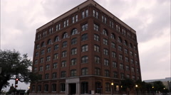 Panning left shot of the Texas School Book Depository at Dealey Plaza, Dallas. Stock Footage