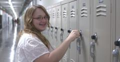 Stock Video Footage of Young teenage girl putting in combination at school locker 4k