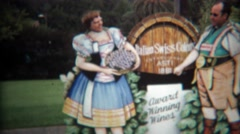 1971: Couple posing at winery in comedy cut out funny business. - stock footage