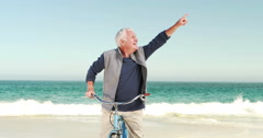 Retired old man on bike pointing the sky Stock Footage