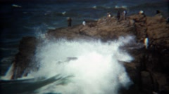 1971: Wave crashes on rocky shoreline almost hitting bystanders. - stock footage