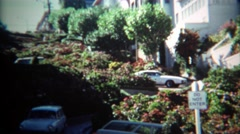 1971: Car turning on curvy famous flower covered Lombard Street. Stock Footage