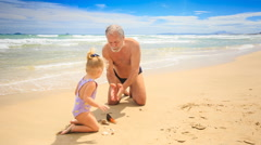 Grandpa Little Blond Girl Model Sand Patty on Wet Beach - stock footage