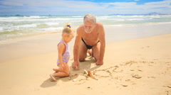 Grandpa Little Blond Girl Sit on Sand Water Washes Drawing out Stock Footage