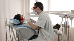 Female patient getting treatment with dental UV light equipment Stock Footage