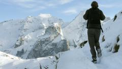 Traveler walking on narrow path in snow covered mountains scenery Stock Footage