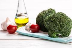Bunch of fresh green broccoli on brown plate over wooden background Stock Photos