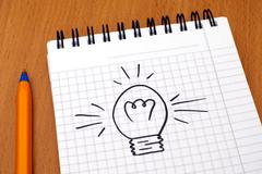 Idea. Light bulb painted on note pad - stock photo