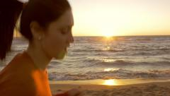 Happy young woman jogging on beach in front of ocean with sunset dolly shot 4 - stock footage