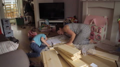 Mother And Son Assembling Flatpack Draws DIY Stock Footage
