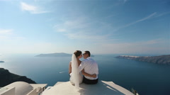 Brunette bride and groom sitting on the terrace and kissing with sea background Stock Footage