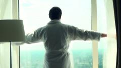 Man unveils curtains and admire view from window, super slow motion 120fps - stock footage