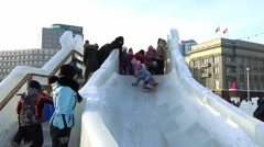 CHILDREN IN ICE TOWN MOVE DOWN FROM ICE SLIDE. CHELYABINSK, RUSSIA. 4 Stock Footage