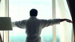 Man unveils curtains and admire view from window Stock Footage