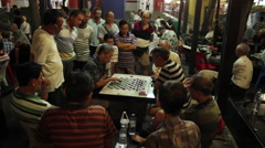 Gathering of men playing checkers or chess at night in Chinatown, Singapore - stock footage