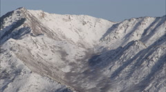 Tilting down shot of snow cover mountains in the Wasatch range to the Rice Stock Footage