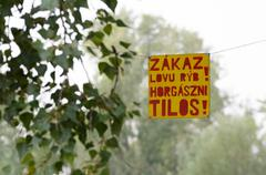 Hanging Sign about Fishing Prohibition Bilingual Slovak and Hungarian - stock photo