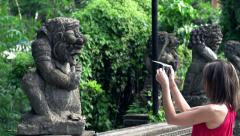Woman taking photo with cellphone of ancient sculpture in park, super slow motio Stock Footage