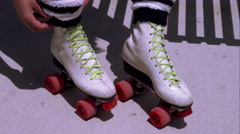 Tight shot of a woman adjusting leg warmers on her roller skates. Stock Footage