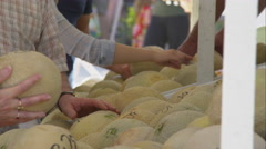 Tight shot of people selecting cantaloupe at a farmers market. Stock Footage
