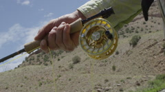 Fly fisher adjusting fishing reel Stock Footage