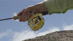 Fly fisher adjusting fishing reel - stock footage