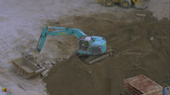 Shot from above of a trackhoe moving large chunks of concrete. Stock Footage