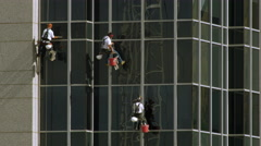 Tight shot of three window washers on lines washing a highrise building. Stock Footage