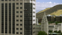Three window washers on lines washing a highrise building. LDS Salt Lake Temple - stock footage