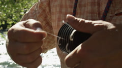 Man adjusting fly line in fishing reel Stock Footage