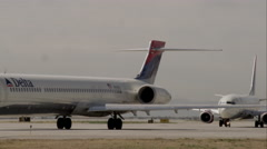 Static shot of two commercial airliners trucking on the runway. - stock footage