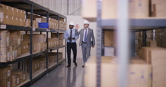 4K 2 Businessmen in discussion as they walk through industrial warehouse Stock Footage