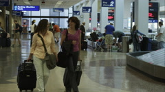 Two women walking the airport at baggage claim. Stock Footage