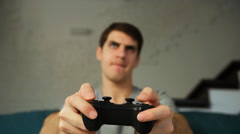 Excited young man playing video game on sofa - stock footage